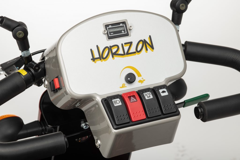 Mobility scooter tiller. Soft easy push buttons show front lights, hazard lights, horn and speed settings. There is also a battery indicator