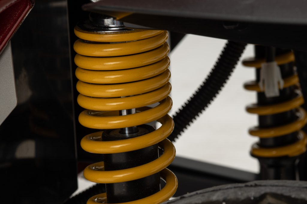 Close up photograph of suspension. The springs are yellow